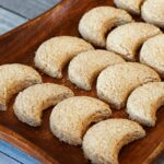 Halfmoon coconut cookies served on a wooden tray