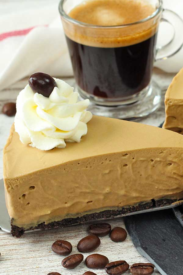 no bake coffee cheesecake portion on a table with a shot of expresso and some coffee granules