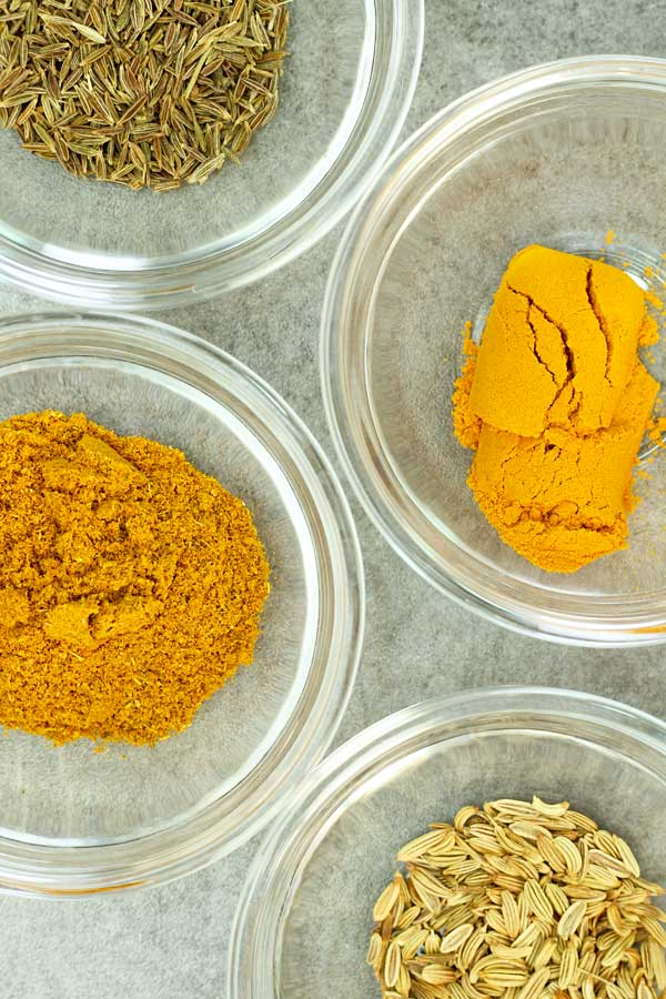 curry powder, turmeric powder, fennel seeds and cumin seeds in bowls