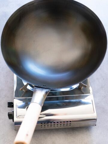 a carbon steel wok just seasoned over a stove
