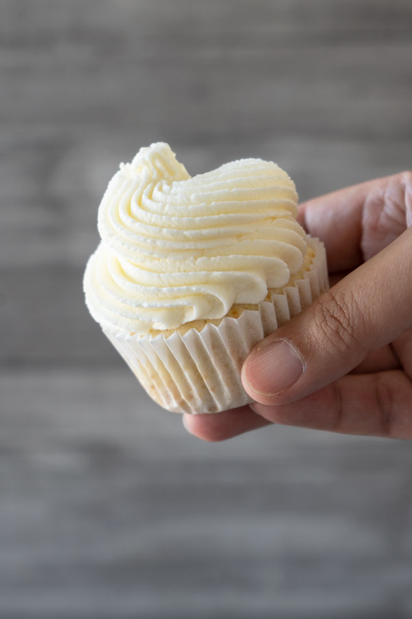 holding a cupcake with white frosting