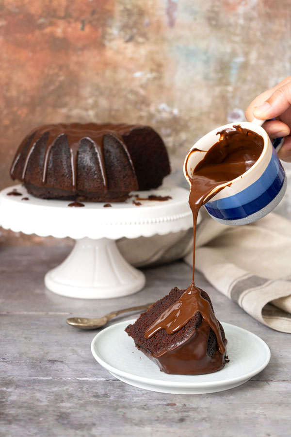 pouring chocolate sauce over chocolate cake portion