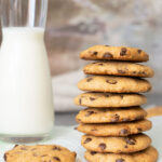 stacked chocolate chip cookies with a glass of milk