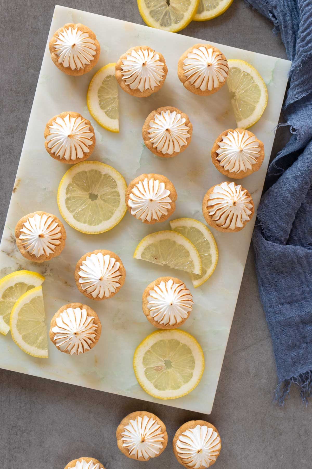 lemon meringue pie bites and lemon slices on a marble table