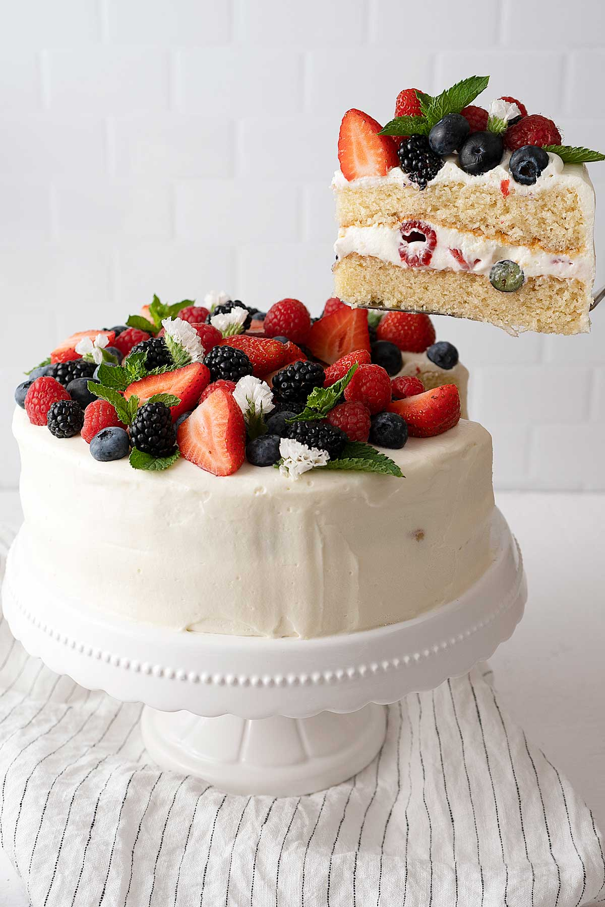 Serving a berry cake with white frosting