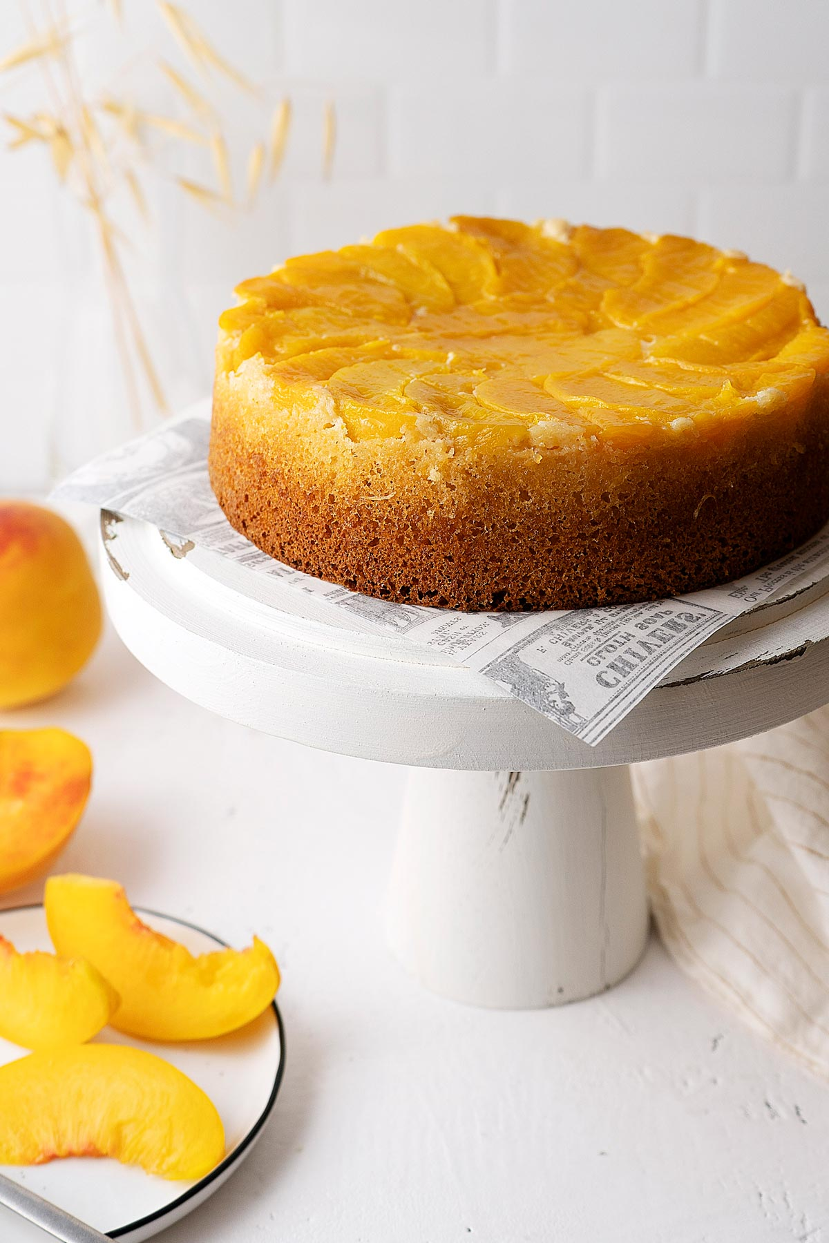 upside down peach cake on a white stand