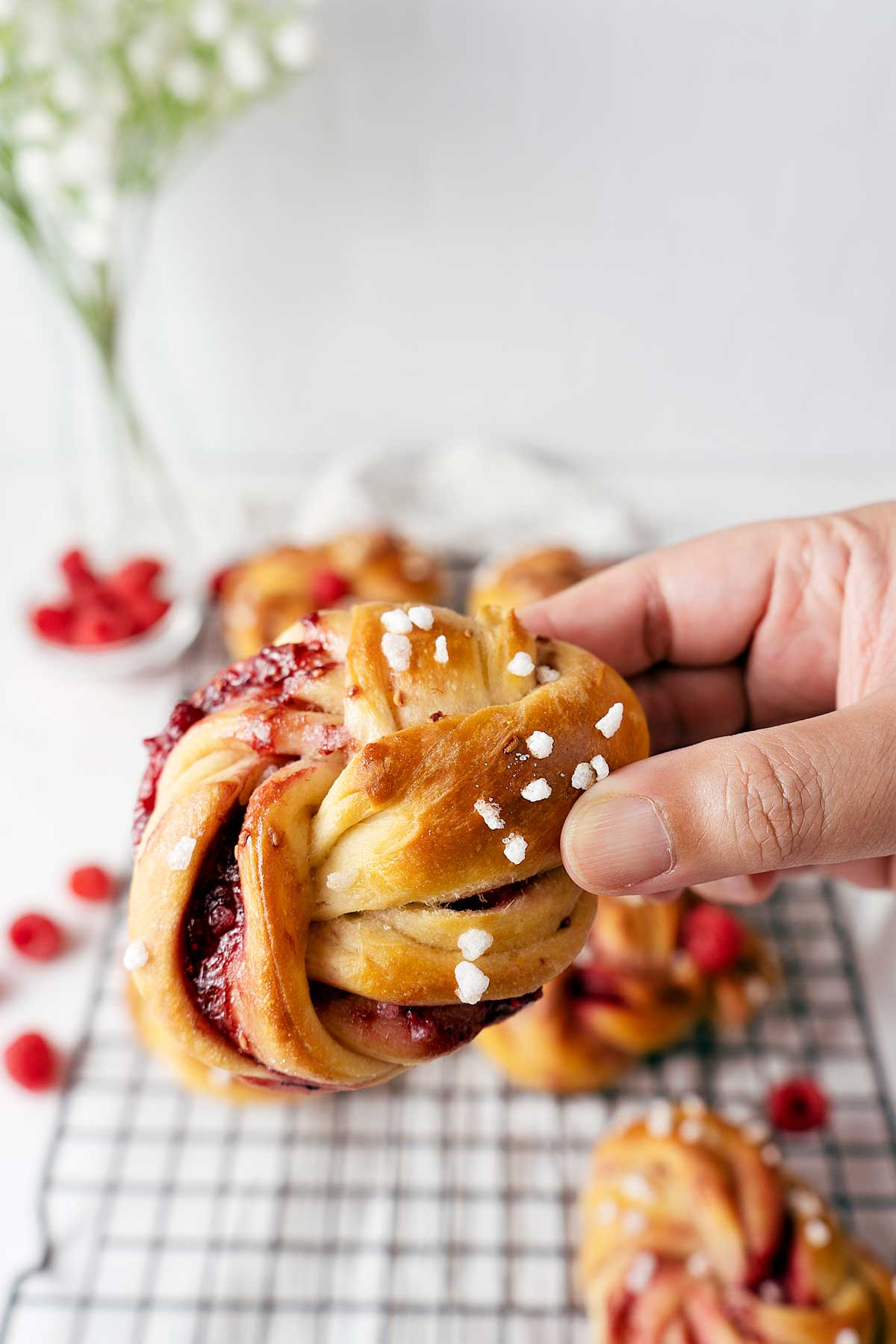 holding a raspberry twisted bun