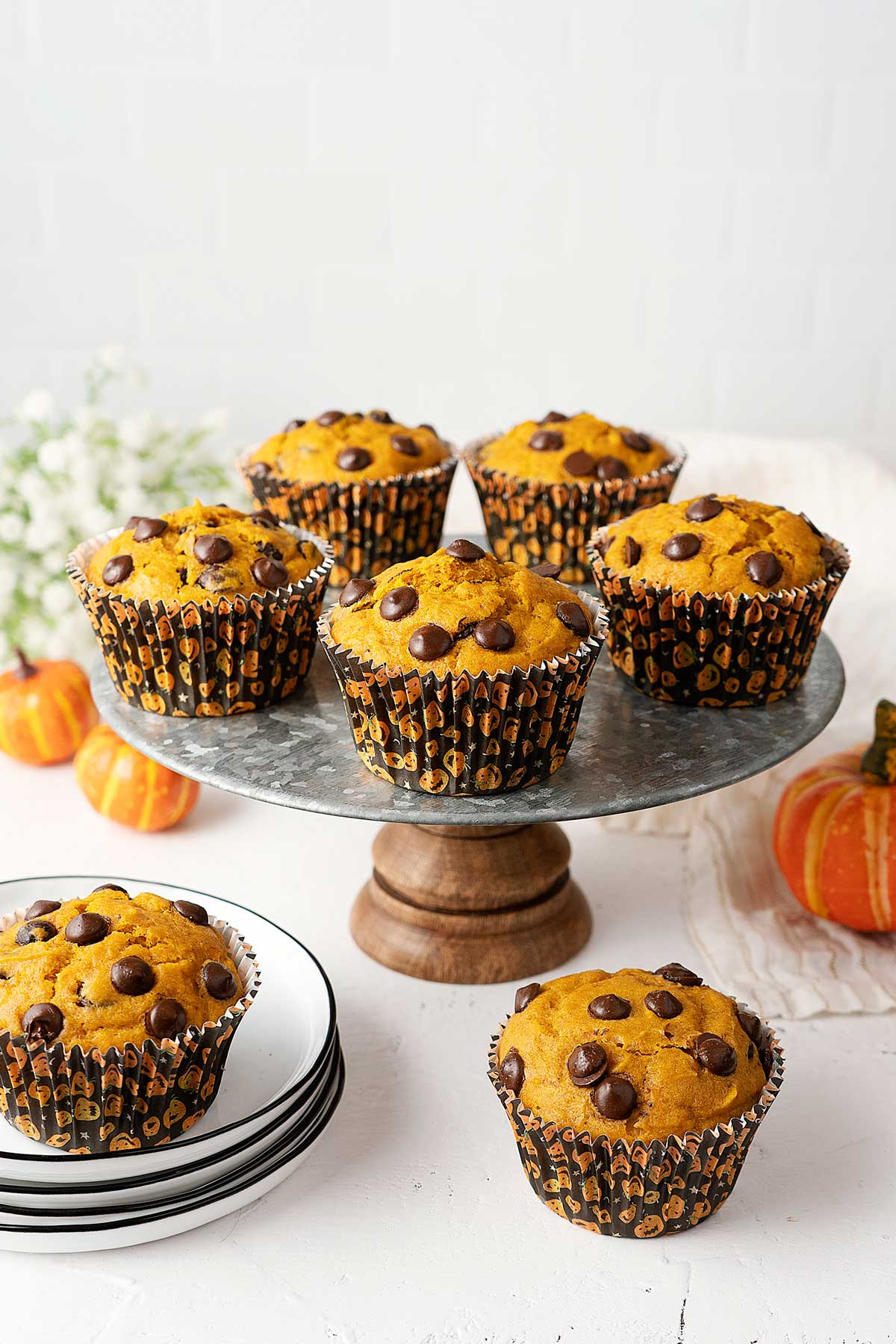 pumpkin chocolate chip muffins on a cake stand.