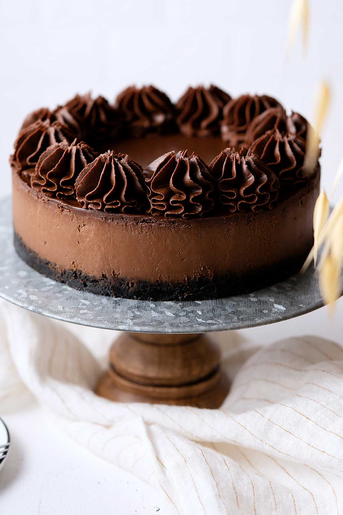 chocolate cheesecake on a cake stand.