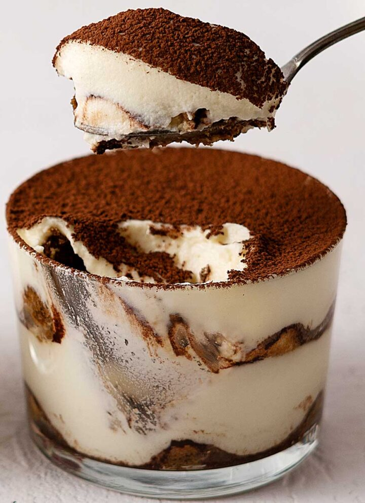 scooping tiramisu from a glass.