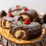 mini yule logs decorated on a wooden table.