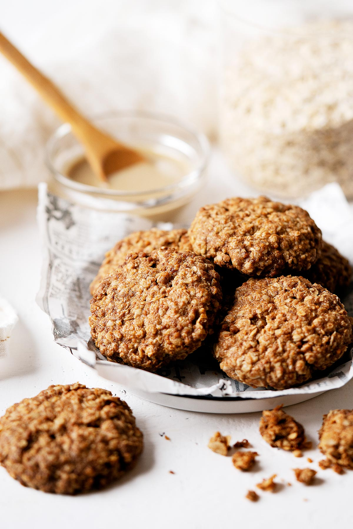 Some healthy tahini cookies on a plate with broken ones on the side