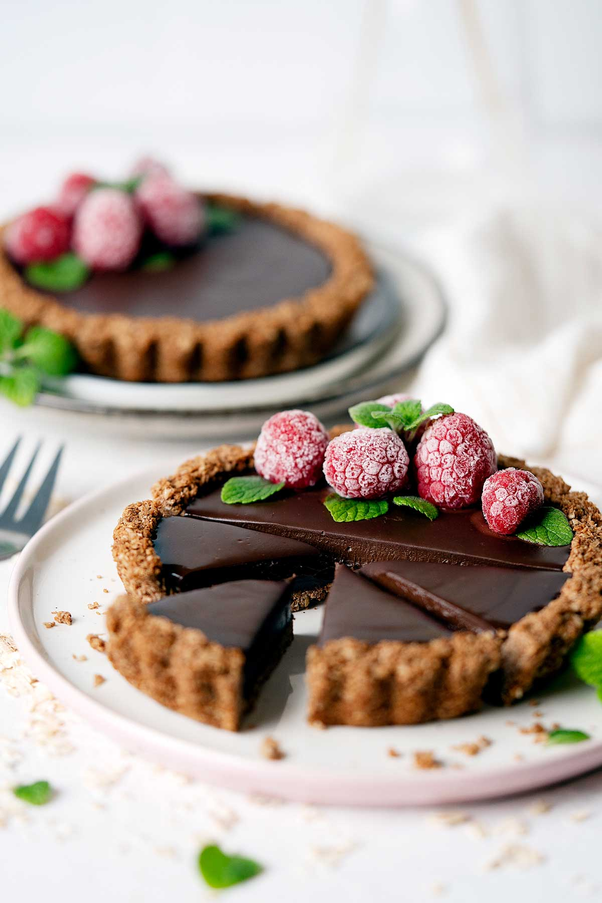 Healthy chocolate coconut tarts with a few slices view from front