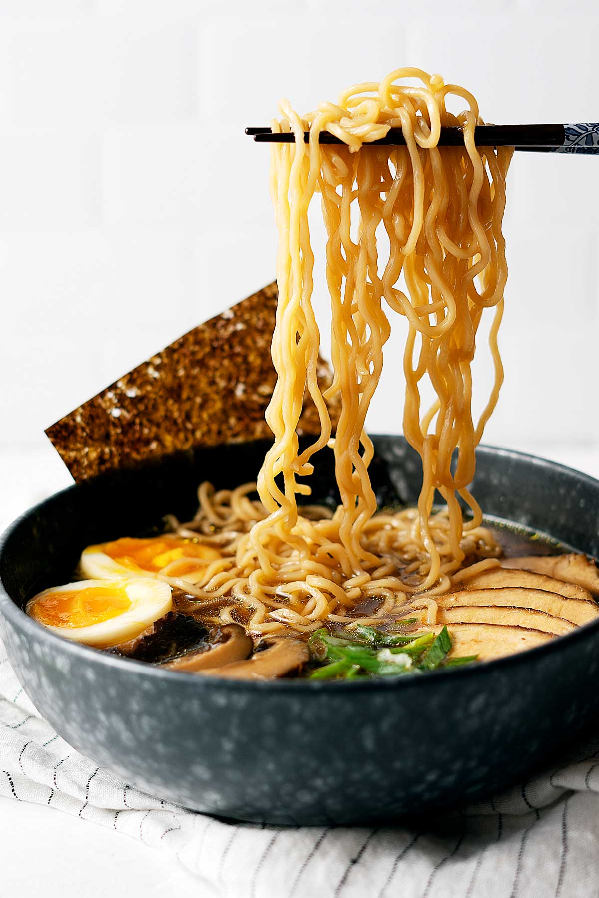 Picking up noodles from a bowl of quick 30 minutes chicken ramen with chopsticks