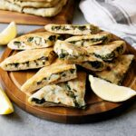 Slices of spinach and feta gozleme on a wooden plate