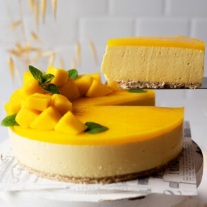 Taking a slice of healthy no bake mango cheesecake from a cake stand
