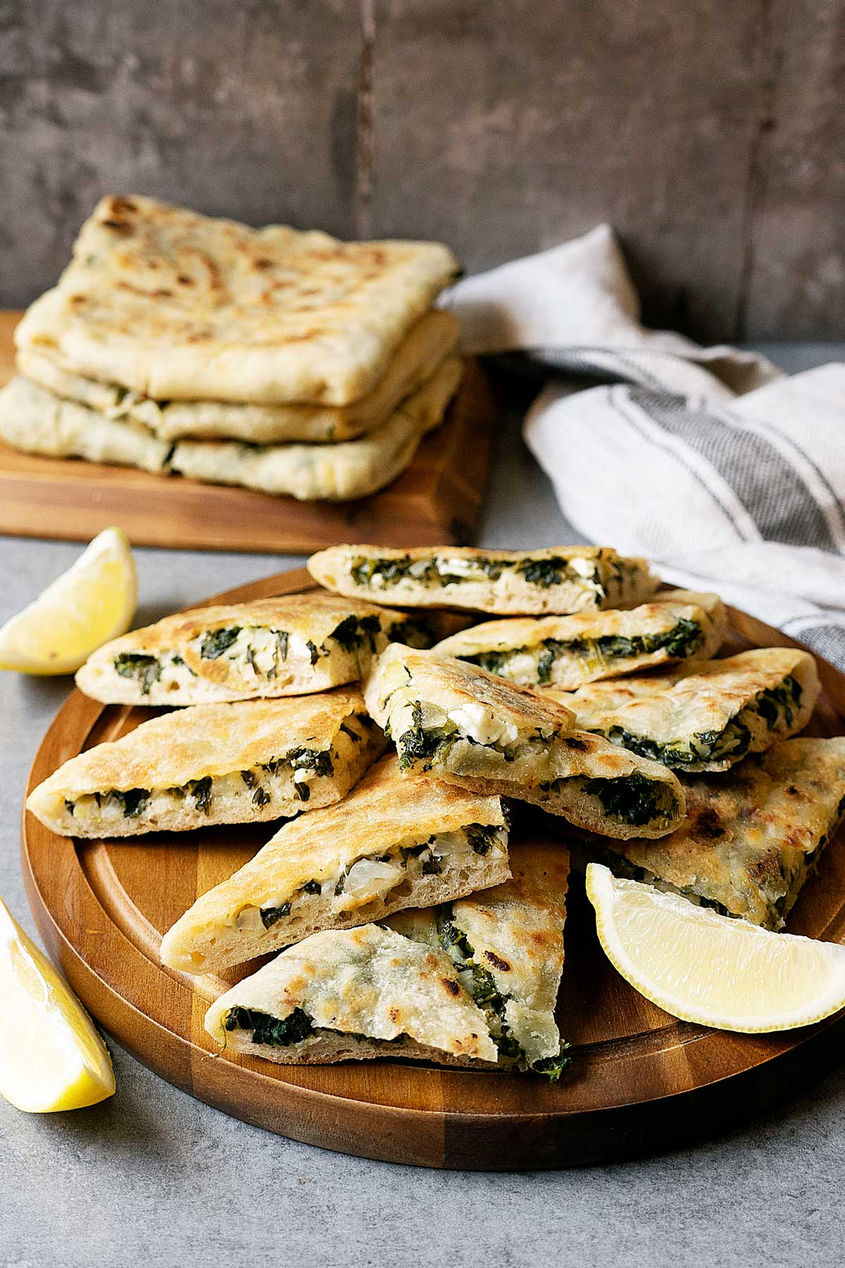 Some slices of spinach and feta gozleme on a wooden table with wedges on lemon