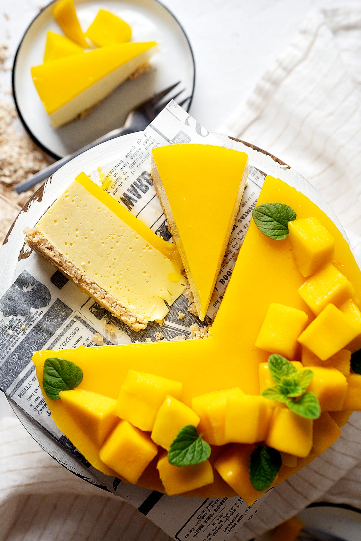 Slices of healthy no bake mango cheesecake on a cake stand together with the rest of it