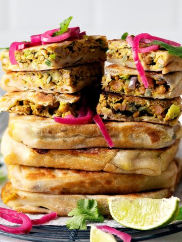 Whole and slices of chicken murtabak flatbreads stacked