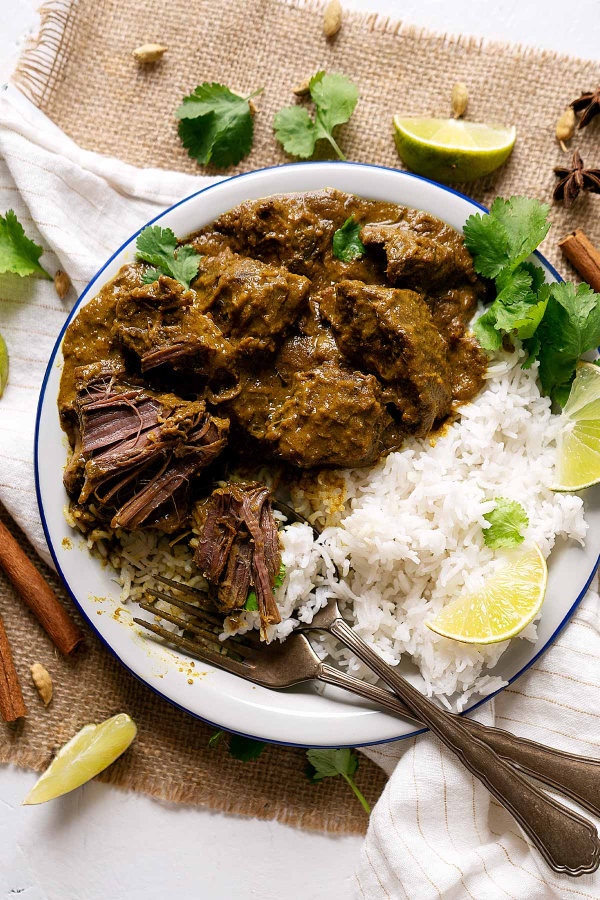 Half eaten slow cooker beef rendang in a plate with some rice