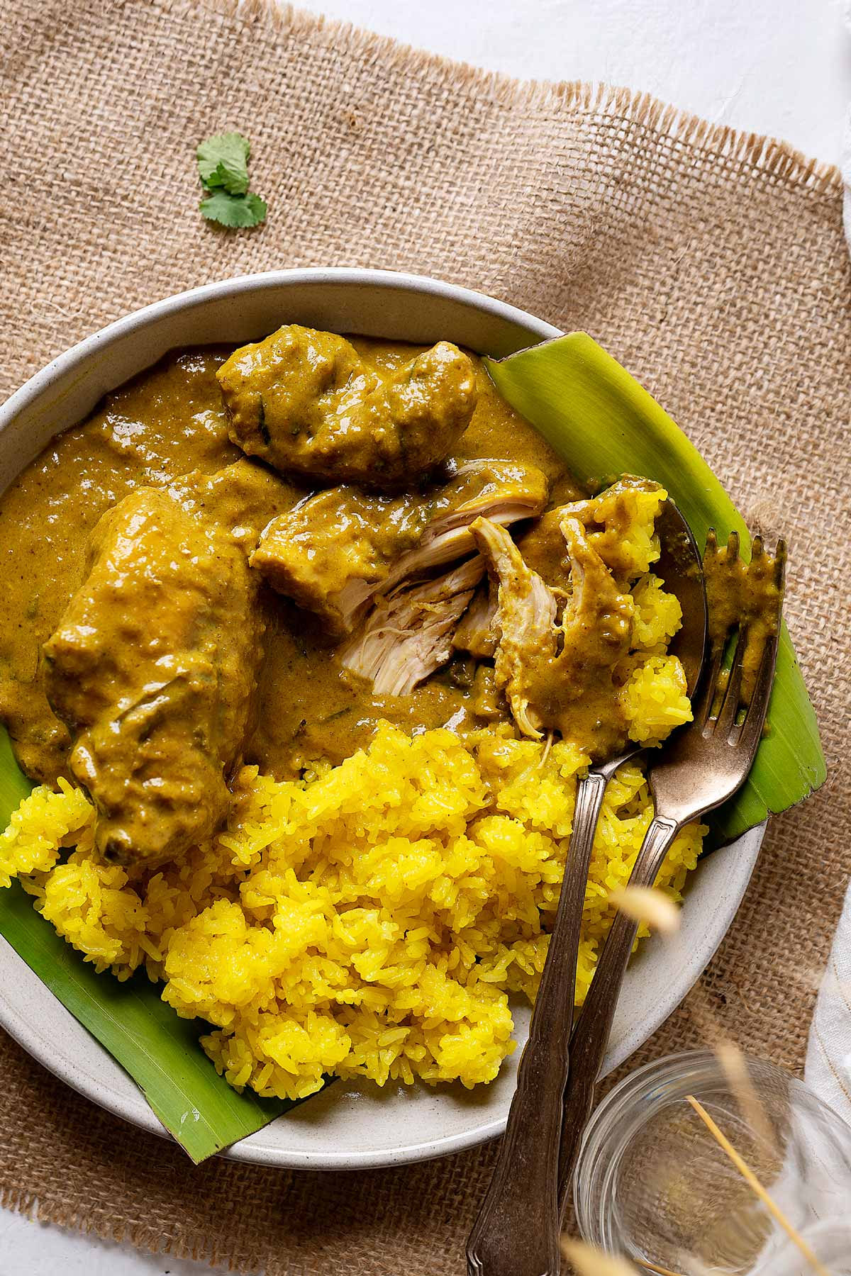 Half eaten slow cooker chicken rendang in a plate with some turmeric glutinous rice