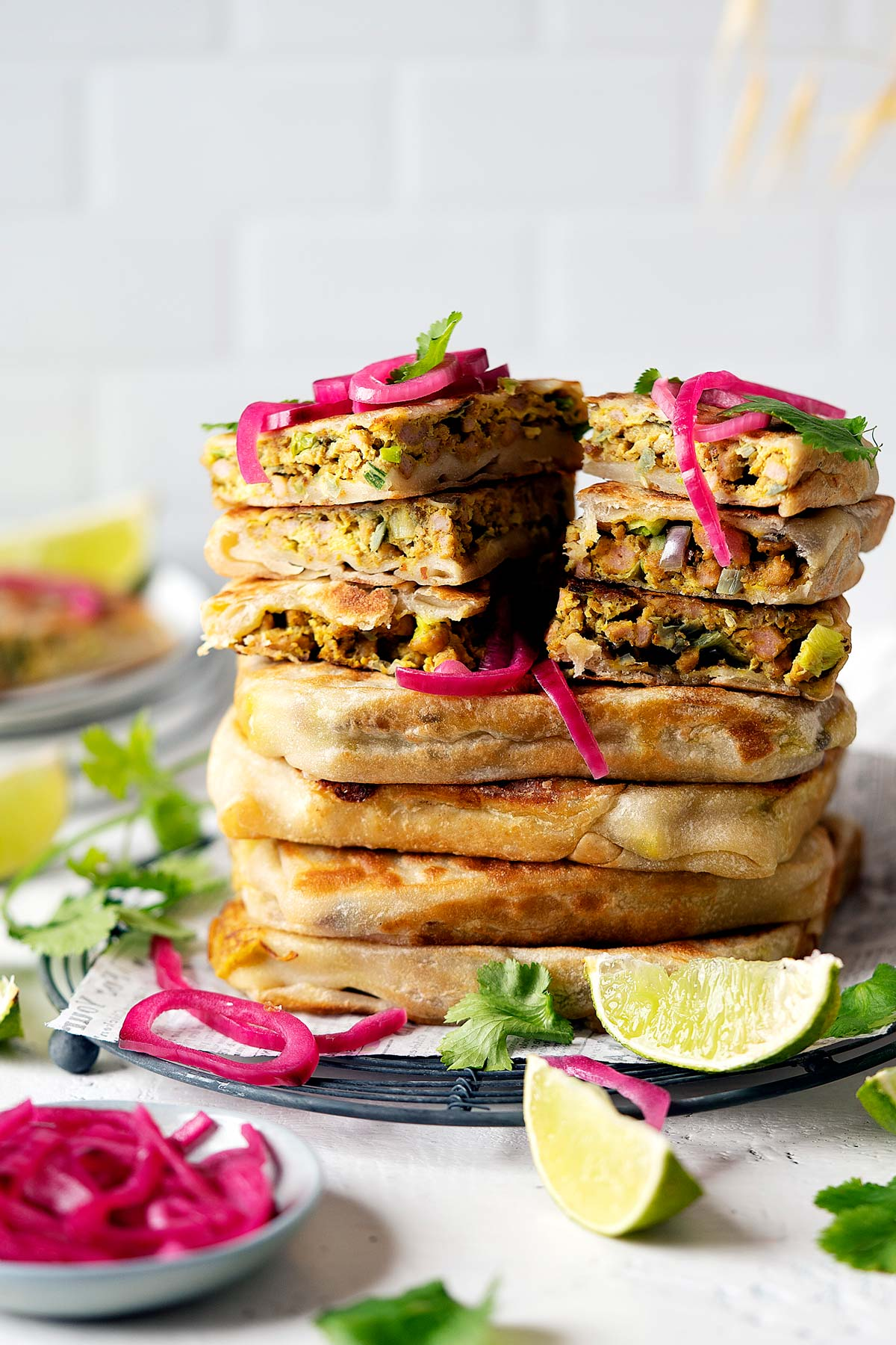 Whole and sliced chicken murtabak flatbreads stacked