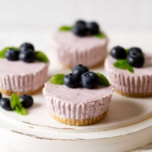 mini blueberry cheesecakes on a cake stand.