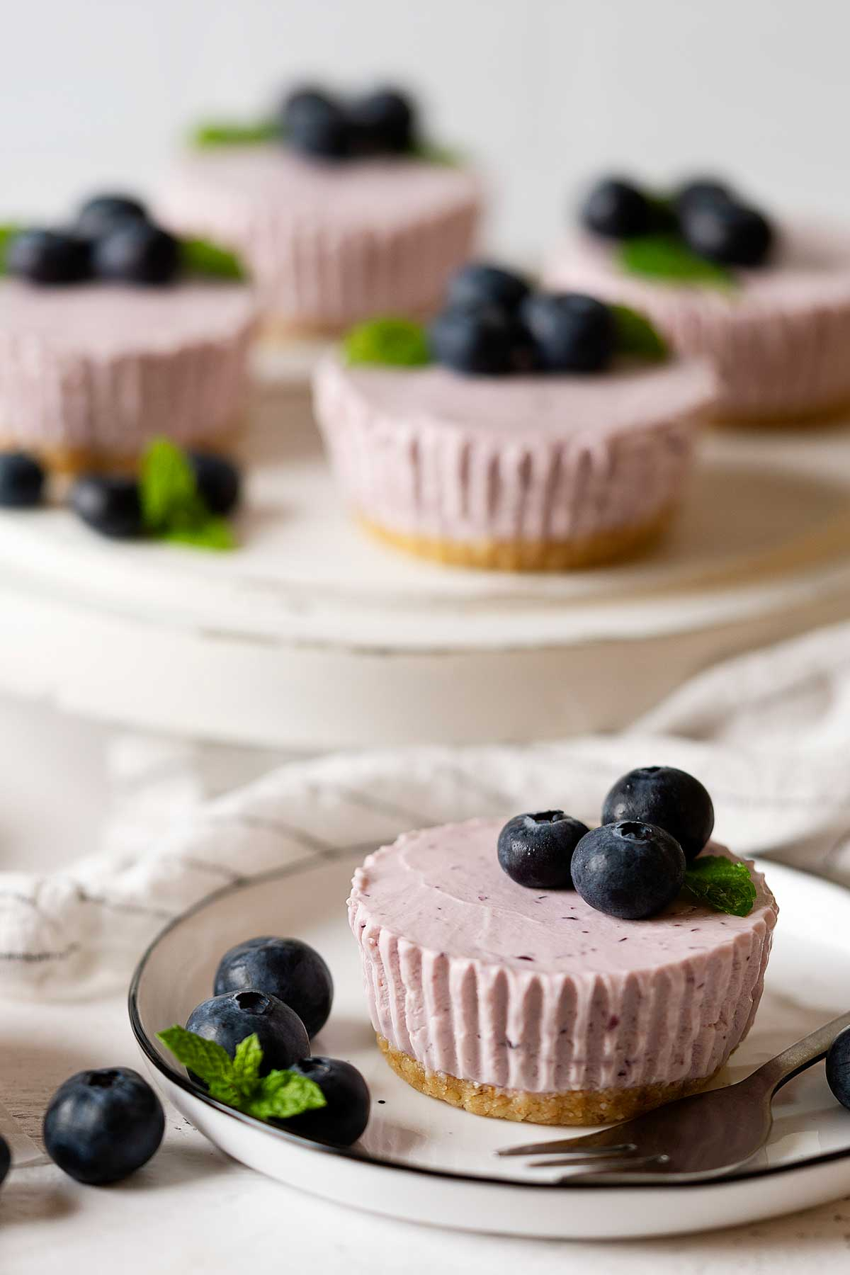 mini blueberry cheesecakes on a stand and plate.