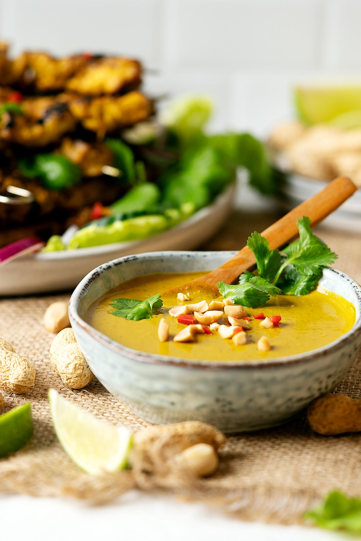 Peanut satay sauce in a bowl with some chicken satay in the background