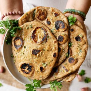 Holding a plate of whole wheat garlic naan