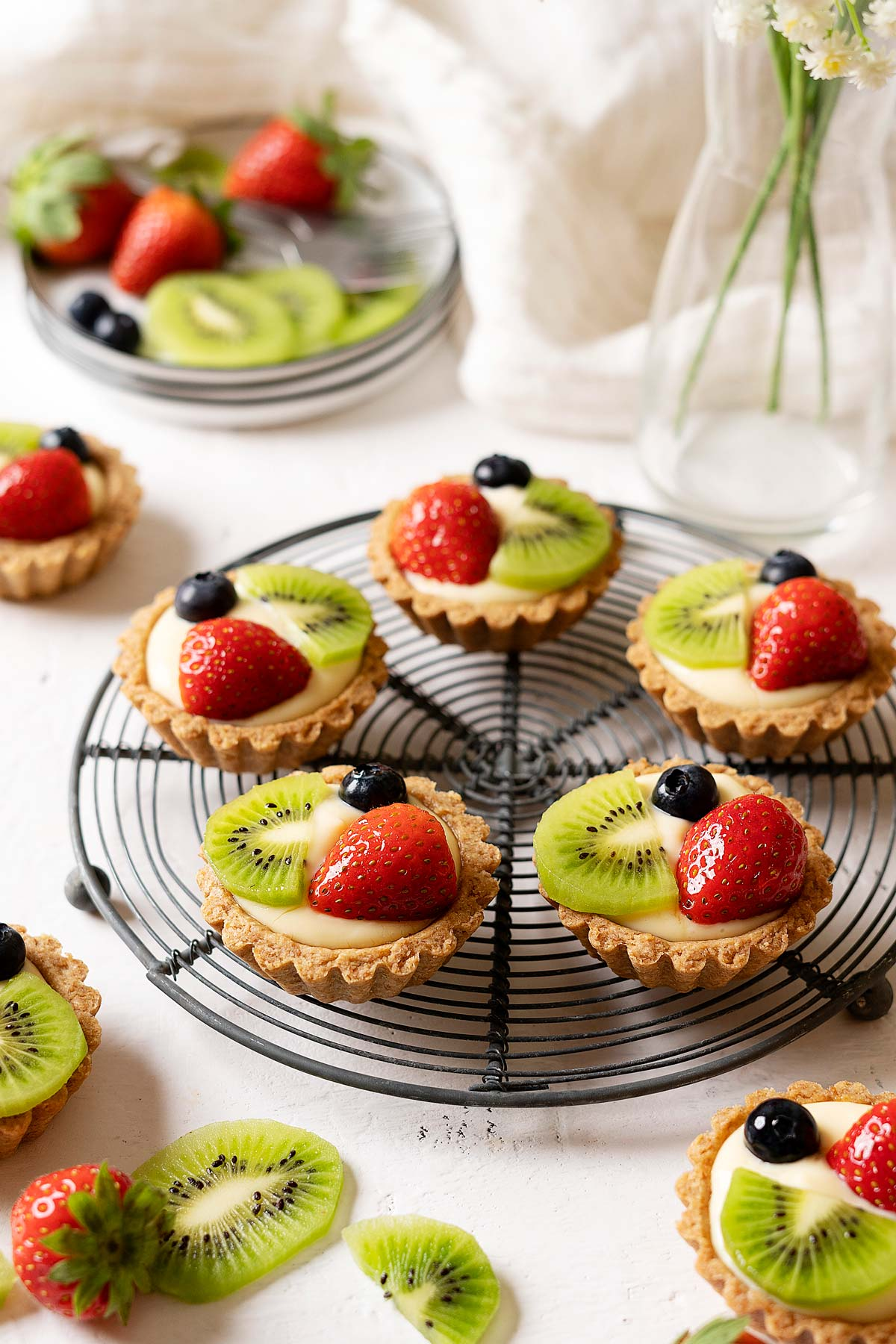Healthier fruit tarts on a rack with fruits in the background view from front