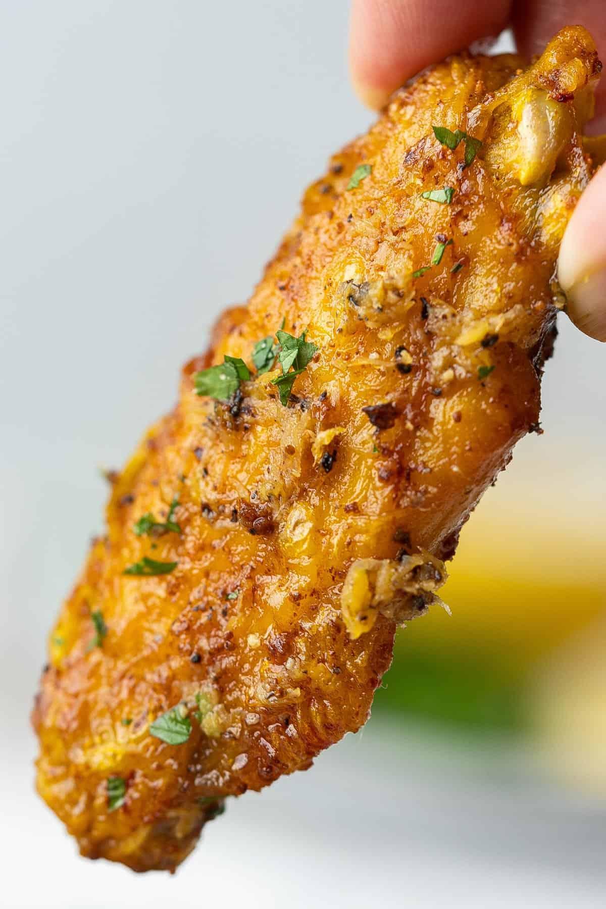 Holding a crispy baked lemon pepper chicken wing