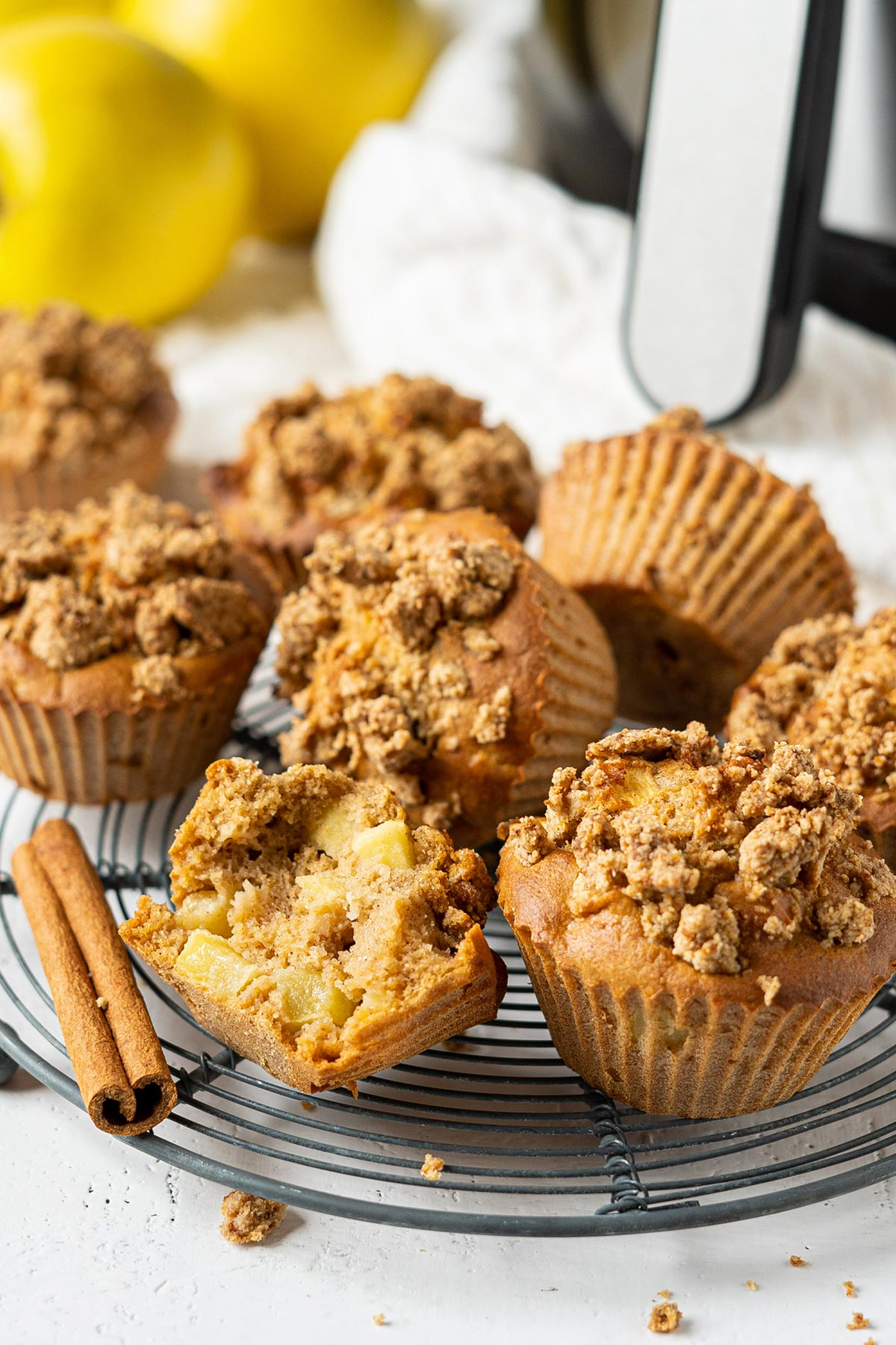 Air fryer apple crumble muffins with one half eaten on a rack