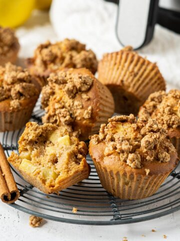 A rack of air fryer apple crumble muffins with one half eaten
