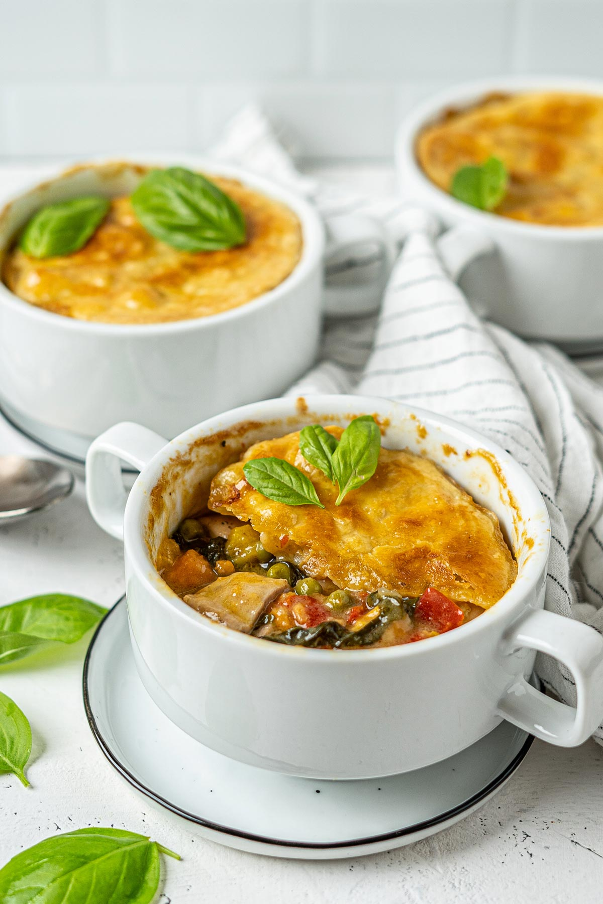 Individual basil chicken pot pie in bowls with one is half eaten